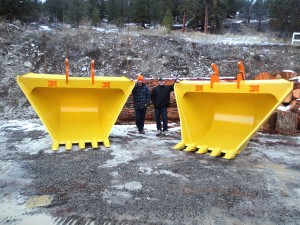 Kevin, owner of Tysea Manufacturing and Tyler standing next to two large heavy duty excavator v-buckets