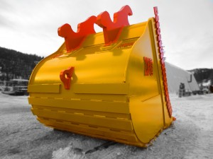 Excavator dig bucket manufactured by Tysea Mfg.  Painted yellow with replaceable orange pin on teeth and bolt on cutting edges