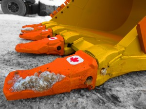 Excavator dig bucket manufactured by Tysea Mfg.  Painted yellow with replaceable pin on teeth and bolt on cutting edges