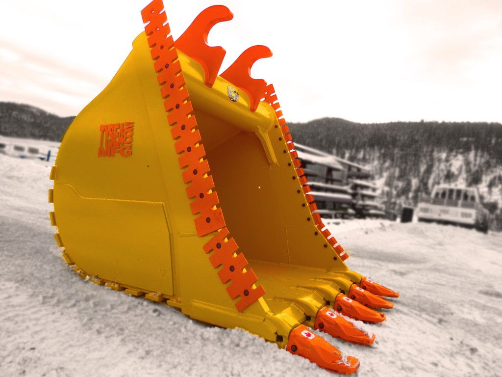 Excavator dig bucket manufactured by Tysea Mfg.  Painted yellow with replaceable pin on teeth and bolt on serrated cutting edges
