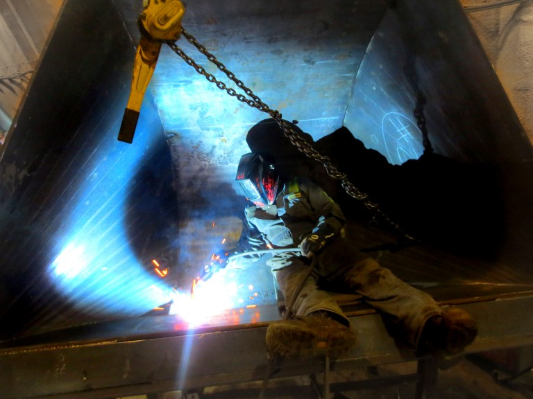 Owner of Tysea Mfg welding inside a large V-Bucket