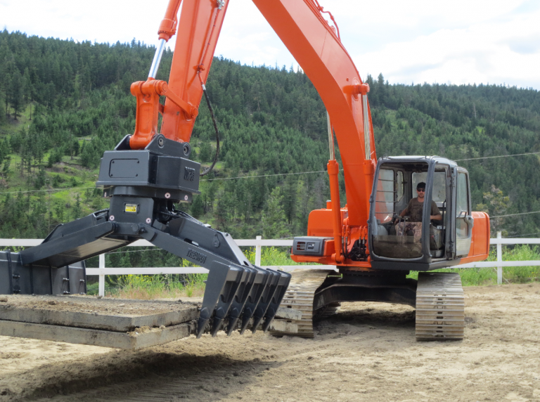 Hitachi excavator newly painted orange with Tysea's heavy duty excavator mat grapple installed.  Testing equipment with swamp mats.