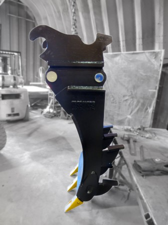 Side profile of excavator mounding rake with dual kickers and quick coupler system installed.