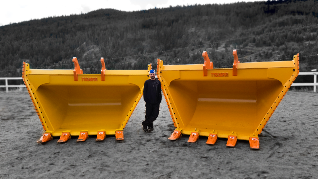 Shop manager posing with two large heavy duty yellow v buckets manufactured by Tysea Mfg.  Orange cutting edges and replaceable teeth.