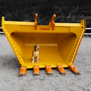 Husky cross lab dog sitting inside a large excavator v bucket manufactured by Tysea Mfg.  Painted yellow with orange cutting edges and orange replaceable teeth.