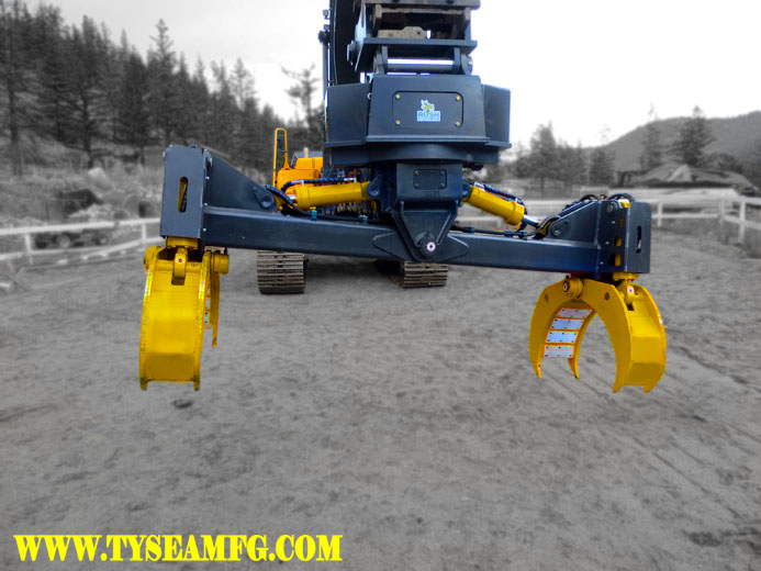 Excavator pipe handler or pipe grabber.  Painted dark grey with yellow grabber arms, cylinders and logos.