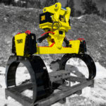 Excavator Pipe handler. Rotating pipe grabber, with yellow grabber arms for simple maneuvering and placement of pipes and poles.  Manufactured by Tysea Mfg.