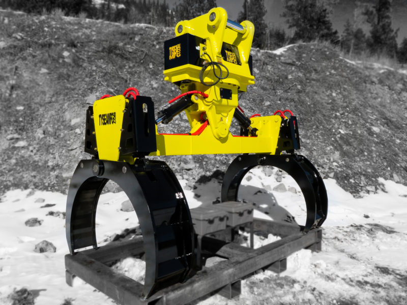 Heavy duty excavator utility handler attachment.  Pipe and pole grapple for placing and handling pipes and utility poles.  Painted yellow with black grabber arms.  Manufactured by Tysea Mfg.