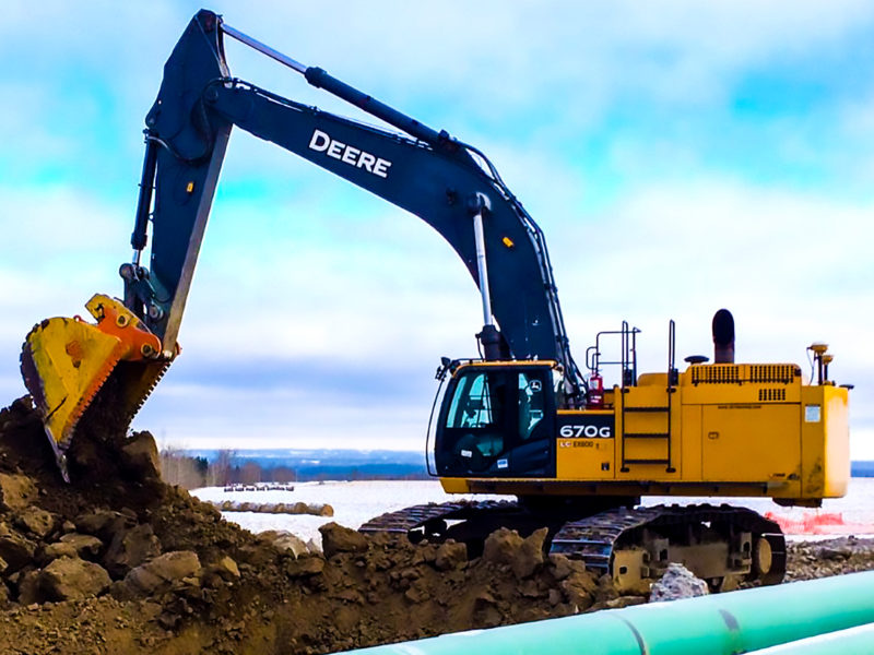 Heavy duty dig bucket manufactured by Tysea Mfg installed on a 670 G John Deere excavator digging near a pipeline installation