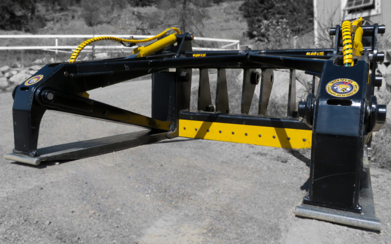 Custom wheel loader pipe handler for wood poles manufactured by Tysea Mfg.  Can be custom manufactured to handle any diameter of wood or steel pipe and poles.