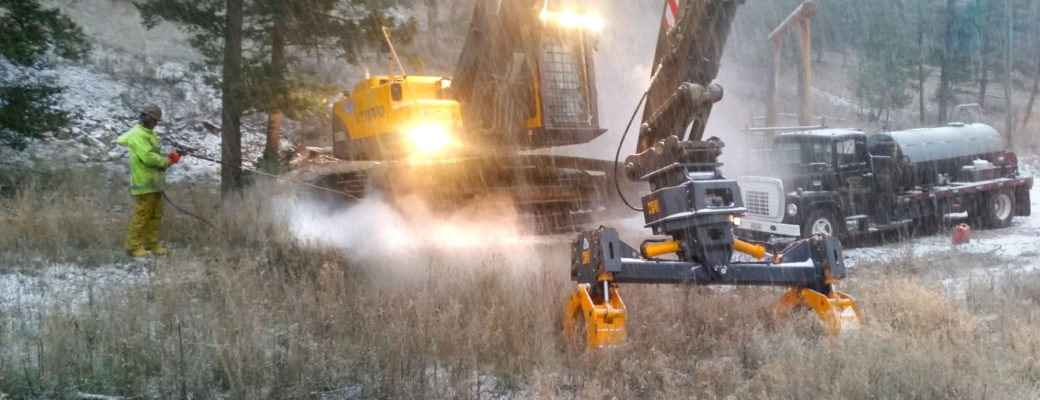 Excavator with pipe handler attachments being pressured washed prior to shipping