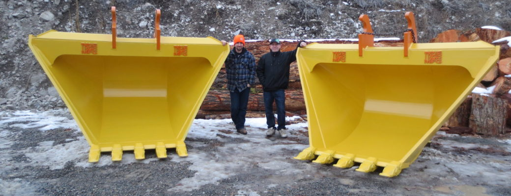 Two excavator ditching v buckets next to the owner and manager of Tysea Mfg